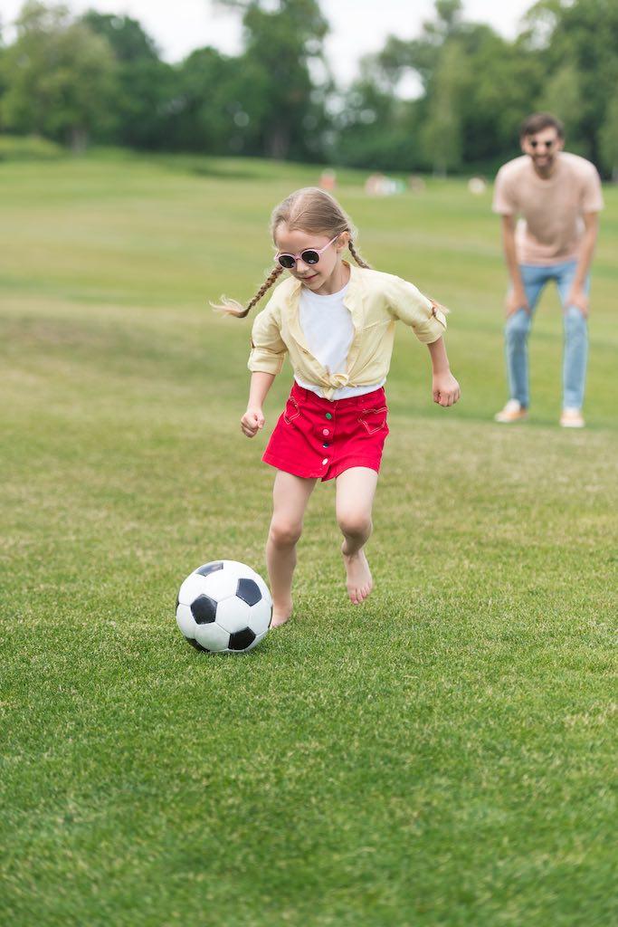 Tüdruk mängib murul jalgpalli. MPKinnisvara arendusprojektid lastega peredele Tallinna lähedal.